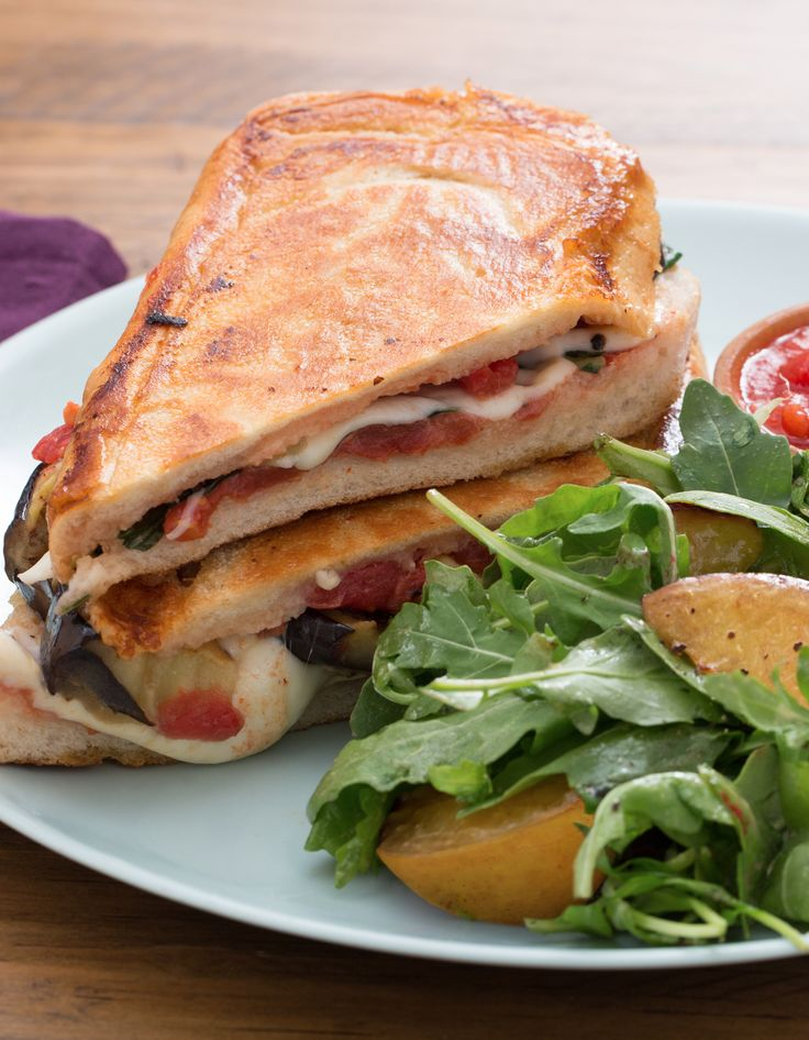 ... eggplant and mozzarella paninis on the stove, using a heavy pot to