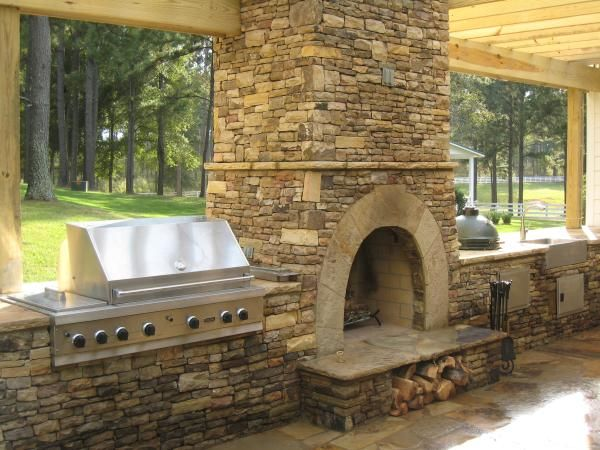 Stone Fireplace Outdoor Kitchen.    Stone fireplace with a nice minimalistic outdoor kitchen with grill and sink.