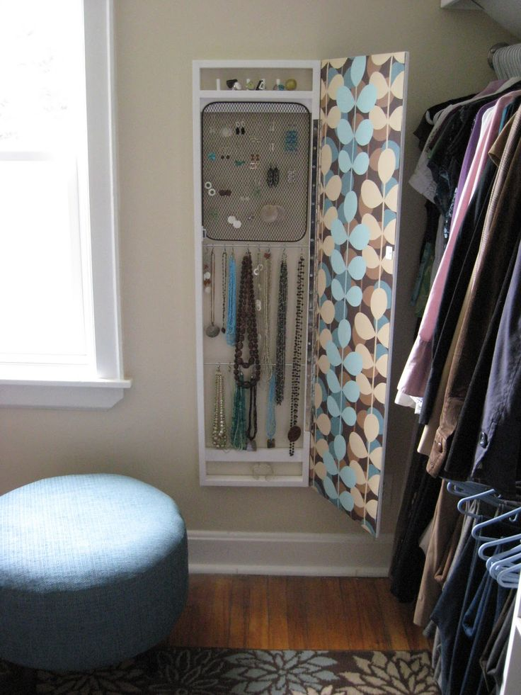jewelry storage behind full length mirror. Rings are stored on pieces of wood dowel set into the pine framework, earrings hang from a metal bbq grill found on clearance and spray-painted brown, and S-hooks are used to hang necklaces from lengths of thin metal rod.
