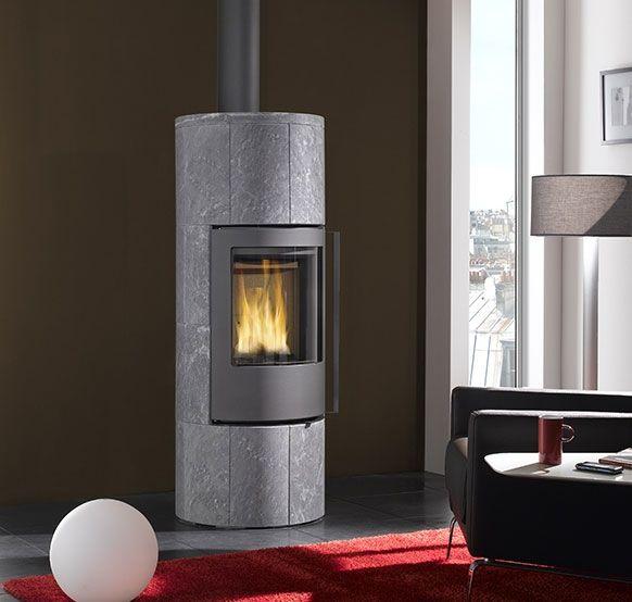 Poêle à bois Turbo Fonte Pallas en pierre ollaire et acier gris. Appareil équipé d'une porte étanche en fonte à fermeture automatique, d'une chambre de combustion en vermiculite moulée haute densité, d'une grille en fonte et d'une gestion de l'air primaire, secondaire et tertiaire par la technolofie Disc'Air. Il affiche une puissance de 8 kW et peut accueillir des bûches allant jusqu'à 33 cm. Il existe également en version L, avec un étage en pierre ollaire supplémentaire.