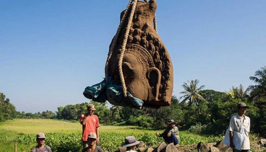 A statue head is hoisted into the air at Banteay Chhmar temple in Banteay Meanchey province after it was unearthed over the weekend. PHOTO SUPPLIED