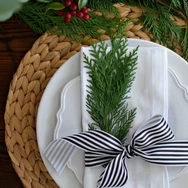 Christmas place setting with fresh greenery & black and white striped ribbon