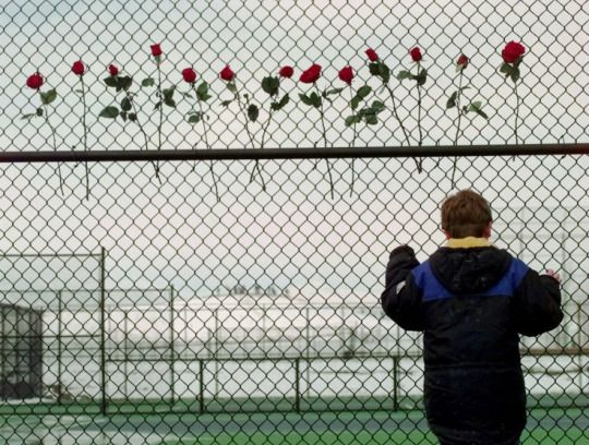 Trench Coat Mafias  A boy looks through the fence at Columbine's tennis courts shortly after the shootings. Thirteen roses were placed there in remembrance of the 13 people killed by the gunmen.