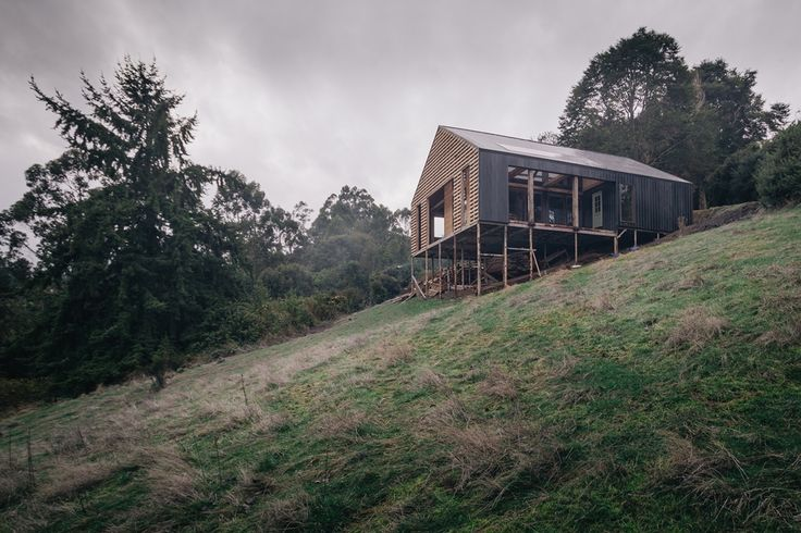 Casa Holmes, en Chiloé En la península de Rilan, frente al canal de Castro, el terreno cautiva por sus vistas y una topografía variada. Desde lo alto según se llega, un coigüe maduro marca su presencia frente a una ladera amplia, despejada y verde.   La galería completa en