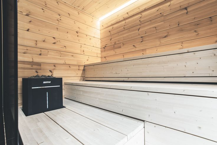 Light sauna interior with black electric heater creates interesting combination. Natural wood and sculptural design of the heater are eye catcher of this interior. #harvia #harviasauna #natural #naturalwood #lightinterior #sauna #electricheater #harviavirta #harviavirtacombi #steamer #asuntomessut #asuntomessut2016