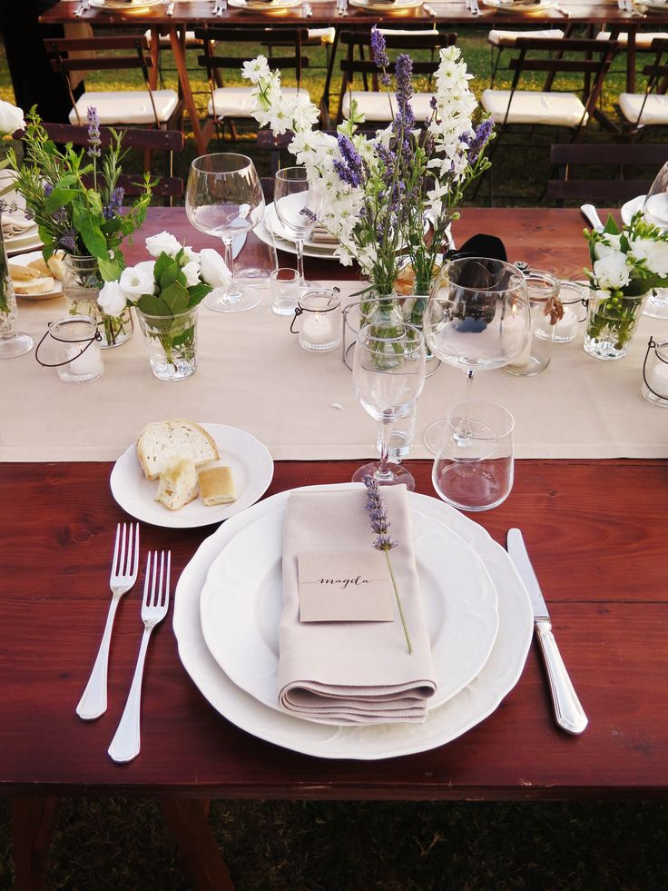 Rustic look with wild flowers, Ivory Charger and plate and silver cutlery on a long wooden table #guidilenci All Rights Reserved GUIDI LENCI www.guidilenci.com