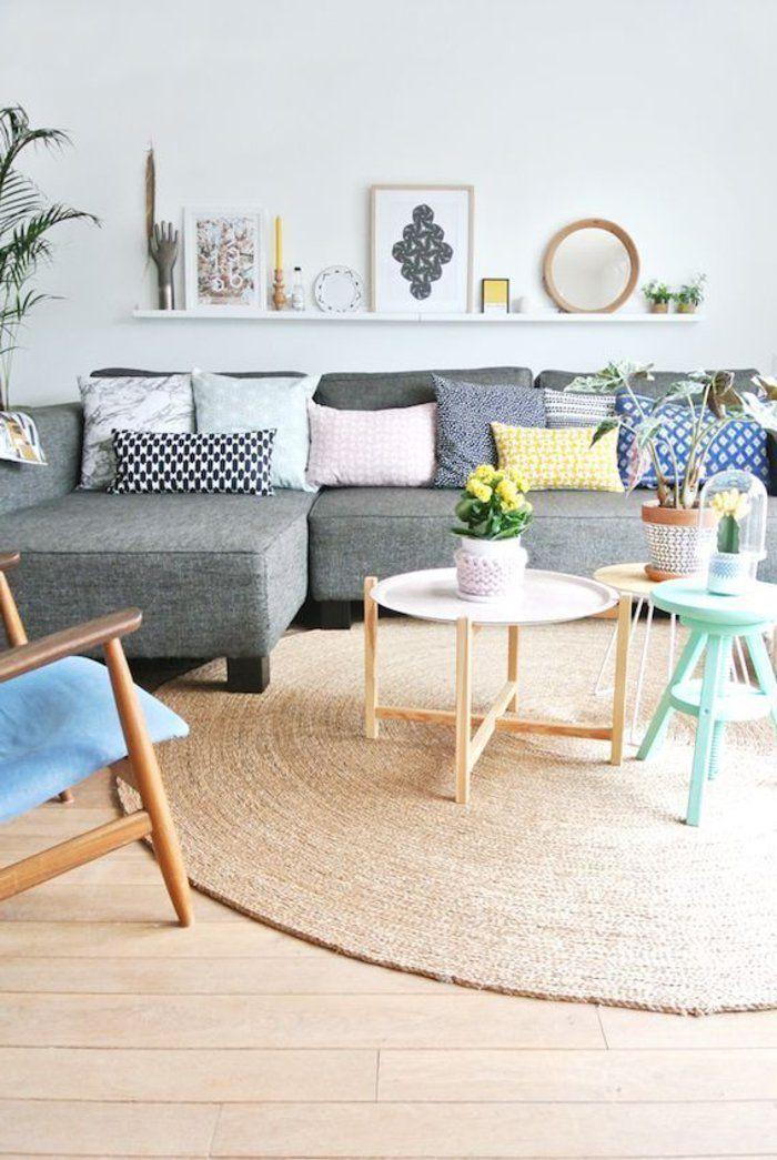Beau canapé d'angle cocooning joliment décoré avec des coussins de différentes tailles, un table basse en bois et une tapis rond en jonc de mer → touslescanapes.com