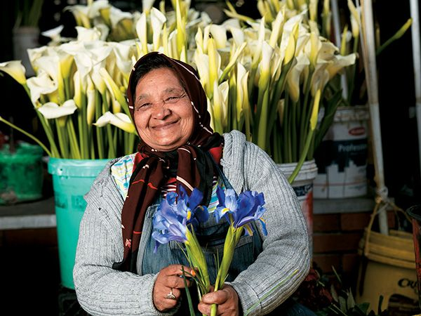 Woman selling freshly cut flowers in Adderley Street, Cape Town. Generations of flower sellers from the same families have run stalls at the Adderley Street market for over 100 years!  WhereToStay Cape Town CBD https://goo.gl/tCR4Kr  Photo via Brand South Africa