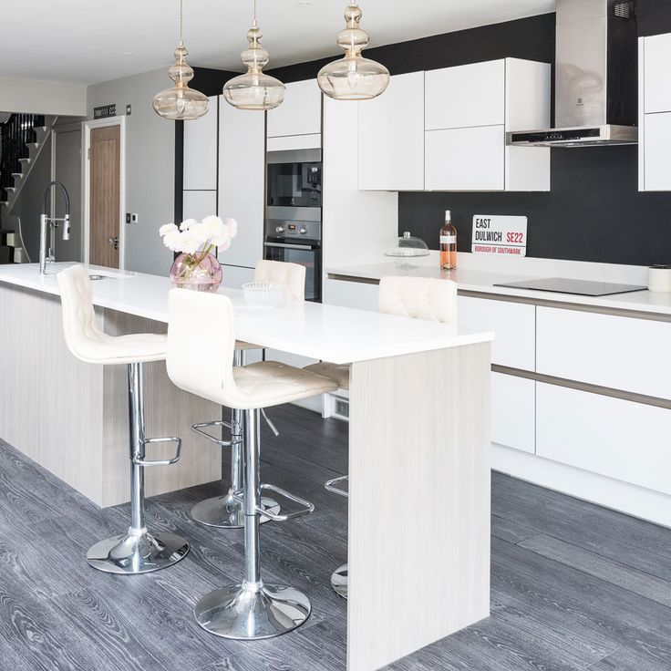 Modern white handleless kitchen with black walls
