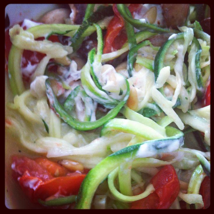 Gezonde spaghetti van courgette: courgetti! Verwarm 2 el kippenbouillon in een pan. Voeg daar 1 teen knoflook en gehalveerde cherrytomaatjes en verse basilicum toe. Rooster de pijnboompitjes in een koekenpan. Was de courgette en maak met de spirelli lange dunne slierten. Strooi er wat zout op. Verhit in een wok wat kokosolie en voeg een teentje knoflook toe. Wok de slierten courgette kort op hoog vuur. De courgetti en kippenbouillon op een bord en geitenkaas en pijnboompitten erop.