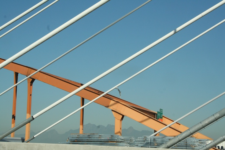 Cable stays of the Superbridge with the steel arch of the original bridge in the background.