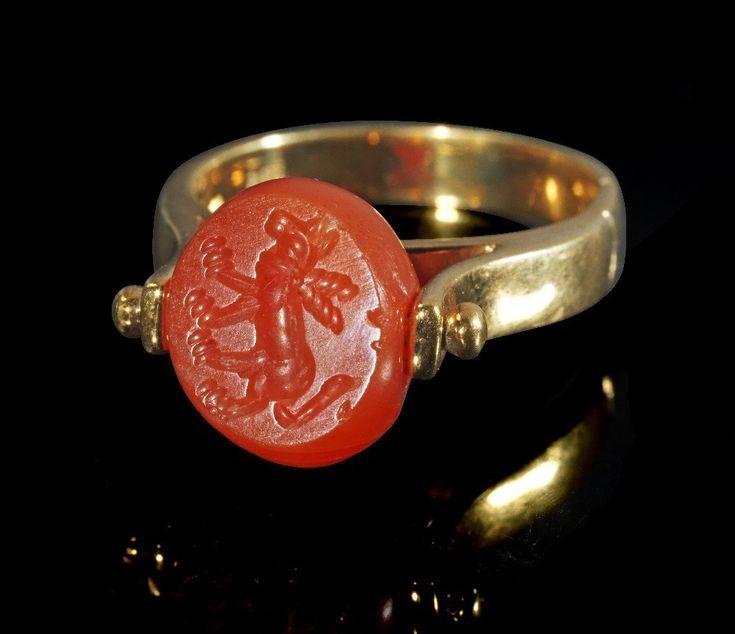 Moderner Goldring mit Kugelsiegel. Kugelsiegel sassanidisch, 5. - 6. Jh. n. Chr. , Ring modern. 8,75g, Umfang 59mm. Gleichmäßig breite, flache Schiene, die oben in zwei Halterungen für das Kugelsiegel ausläuft. Das ellipsoide Siegel (B 1,2cm) besteht aus Karneol, auf dem Intaglio ein Wolf mit einem Band um den Hals. Gold! 585er Gold (Stempel), winzige Splitter des Kugelsiegels fehlen.  Provenienz: Ex Sammlung F.M., Bayern, 1970er Jahre.SIXBID.COM - Experts in numismatic Auctions