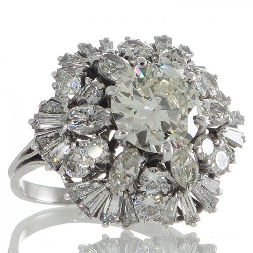 A platinum dome shaped cluster diamond cocktail ring with an elevated central 1.97ct transition cut diamond with six marquise diamonds radiating out from the centre stone each separated by two round brilliant diamonds leading to a scalloped edge of tapered baguettes all above wired basket style underbezel to a triple ribbed band. #Rutherford #Melbourne