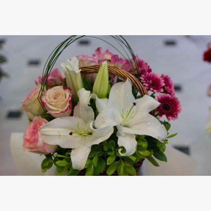 Σύνθεση σε καλάθι με ζέρμπερες, λίλιουμ και τριαντάφυλλα.