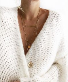 Thick white knit cardigan sweater and layered think gold necklaces.