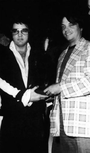 Receiving a plaque from RCA commemorating the pressing of the two billionth record at RCA's Indianapolis pressing plant (which was done during the manufacturing of Elvis' new album, Moody Blue) before his last concert in Indianapolis on June 26, 1977.  Less than two months later, Elvis would be dead.
