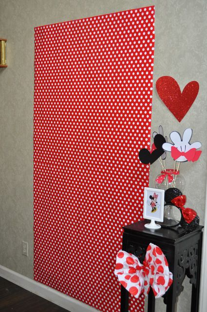 But wrapping paper and designate and area on the wall, make fun props of mickey and minnie ears, Place a garlnd of mickey ears over wrapping paper to create a fun photo area