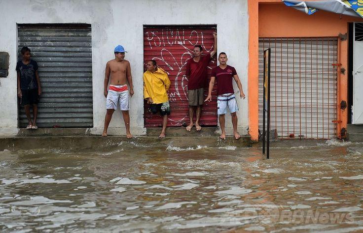 ブラジル北東部レシフェ(Recife)で、豪雨により冠水した道を渡ろうとする人々(2014年6月26日撮影、資料写真 FILE)。(c)AFP/PATRIK STOLLARZ ▼30Jun2014AFP|ブラジル南部で洪水、住民5万人超が避難 http://www.afpbb.com/articles/-/3019152 #Recife #Flood