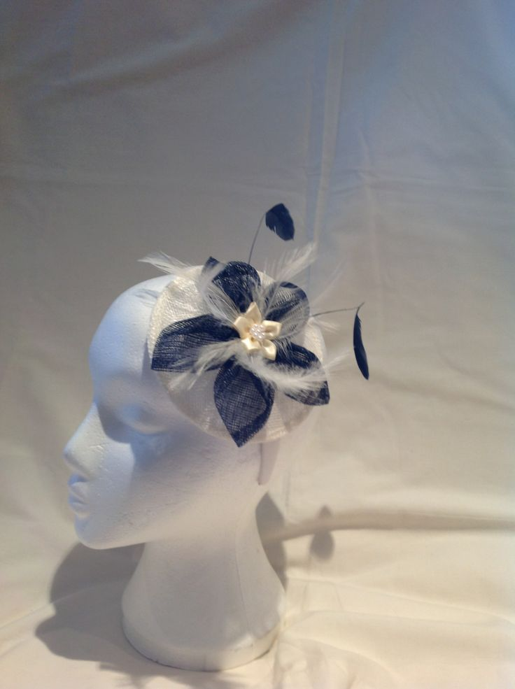 The Sally is a small fascinator on a buttermilk sinamay base with sinamay sapphire blue leaves surrounding a buttermilk silk flower with pearl detailing and matching feathers to finish. $70 AUD.