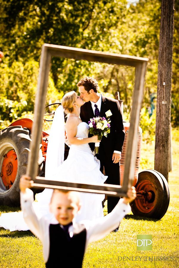 lvoely love wedding photo in photo frame with flower boy holding the frame