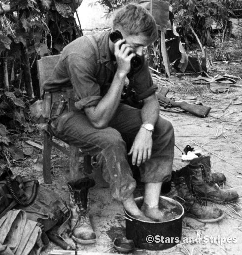 South Vietnam, September, 1966: A Marine radio operator soaks his feet while continuing with his duties during Operation Golden Fleece in Quang Ngai province. The 7th Regiment and the South Vietnamese army's 4th Regiment were in the area to protect the rice harvest from the Viet Cong, who had confiscated about 90 percent of the local crop in each of the previous four years. (Ray Mahon ©Stars and Stripes)