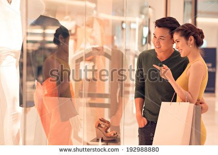 Young woman showing something in the shop window to her husband - stock photo