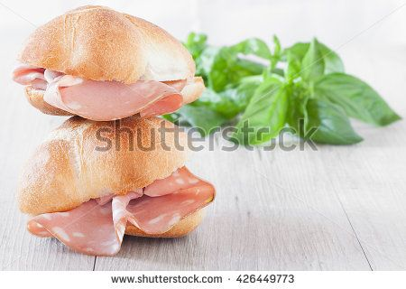 Sandwiches sub with buns and mortadella slices.