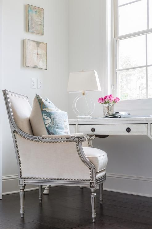 French office features a whitewashed French desk topped with a Ring Form Large Table Lamp, paired with a gray framed bergere chair upholstered in cream fabric placed under windows.