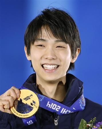 フィギュアスケート男子の金メダルを手に、笑顔を見せる羽生結弦=15日、ソチ(共同)