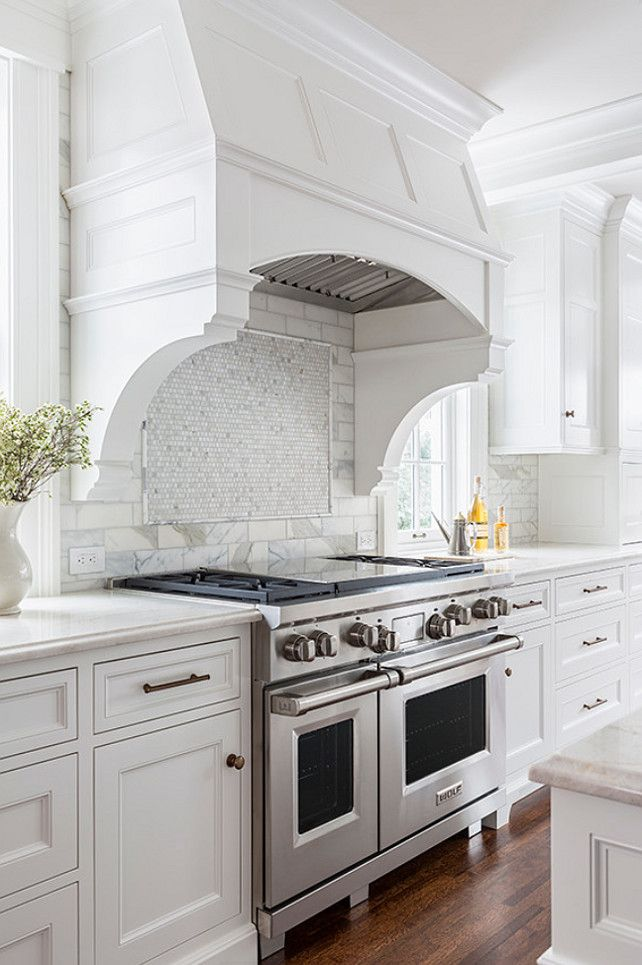 Nice Elegant Kitchen A White Curved Kitchen Hood Accented With Corbels Which  Stands Over A White Mosaic Marble Cooktop Backsplash And Wolf Range. Awesome Design