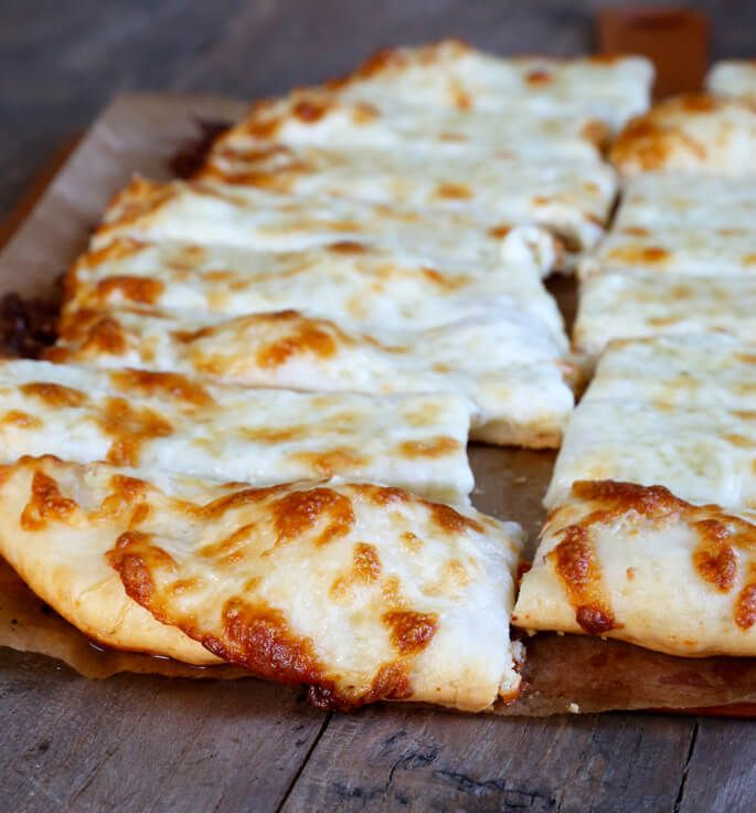 Thick crust pizza dough + tons and tons of cheese + garlic pressed into a gorgeous paste = pizzeria-style gluten free pizza breadsticks.