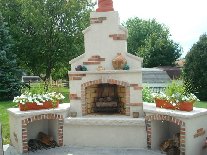 Southwestern design, outdoor woodburning fireplace with log storage. Dryvit & brick with limestone caps & clay chimney, by Kirk Wylie Masonry, Limited