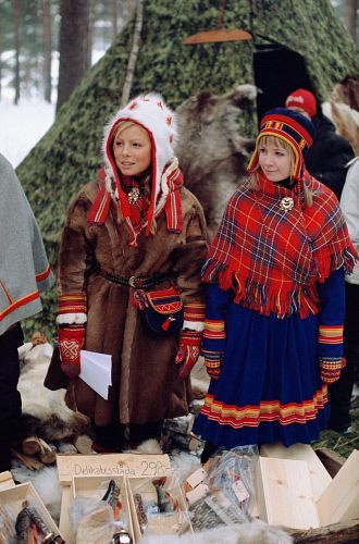 Saami girls in traditional costume sell dried fish at the traditional market. Jokkmokk. Sweden: Sami, Jokkmokk Market: Arctic & Antarctic photographs, pictures & images from Bryan & Cherry Alexander Photography.