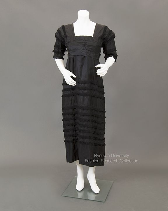 Black silk Directoire-style dress with short sleeves, square neckline. Empire style waist with band, fringe detail on skirt and sleeves. Inner Petersham belt. c.1912. No label. FRC2013.05.002