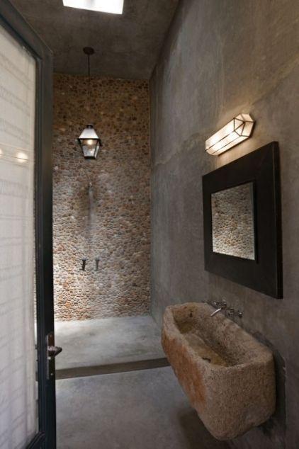 baño rústico, ducha con pared de piedra, pila de piedra como lavabo, suelo microcemento