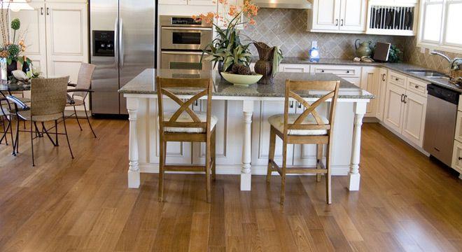 L-shape with island. Oak floors, white cabinets, gray countertops and backsplash