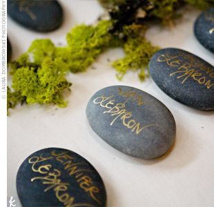 Dark gray river rocks as escort cards. They wrote each guest's name on the stones with metallic gold ink.