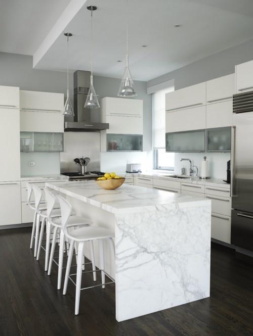 marble waterfall island + glass pendants in modern white kitchen