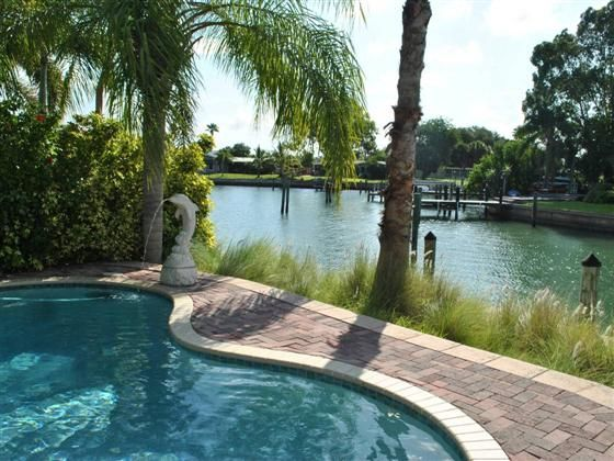 This beautifully maintained home features an incredible private waterfront setting and tropical lush landscape. Open floor plan with polished terrazzo floors and tile crown molding 5 inch baseboards wood blinds beautiful upgraded fixtures and closet organization systems throughout. Tiled kitchen with wood cabinets and panty plus dinette access to large Florida room. Large master suite with walk-in closet and French doors to pool patio. Exterior canvas awnings new roof with transferrable ...