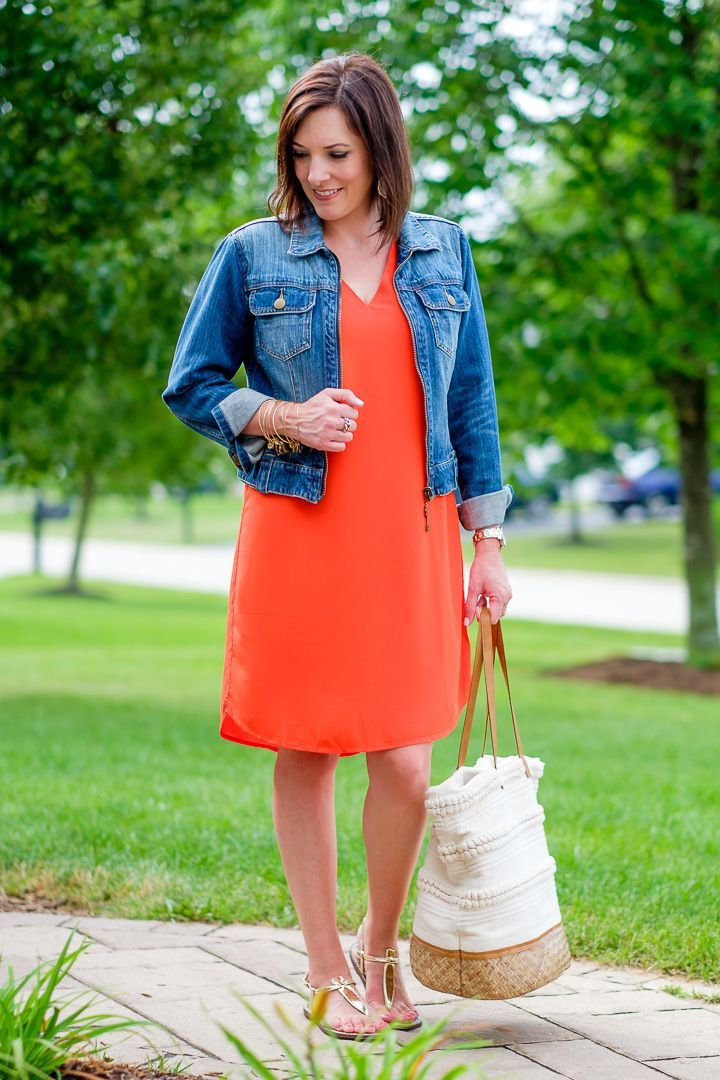 Orange Shift Dress Outfit:  The denim jacket adds a nice point of interest and the blue is a pretty contrast to the orange dress. The gold sandals and woven bottom bag keep it casual but chic. Fashion for the Modern Mom | Jo-Lynne Shane