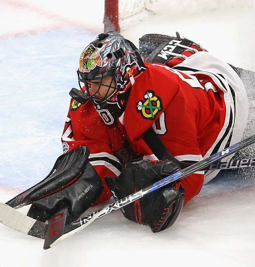 CHICAGO, IL - NOVEMBER 01: Corey Crawford #50 of the Chicago Blackhawks makes a save off of his facemask against the Philadelphia Flyers at the United Center on November 1, 2017 in Chicago, Illinois. The Blackhawks defeated the Flyers 3-0. (Photo by Jonathan Daniel/Getty Images)