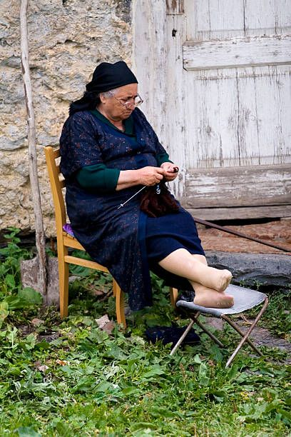 Woman knitting outside her house.