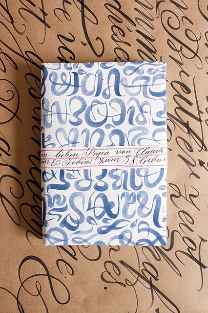 a pretty package wrapped in hand-lettered blue and white paper, place on hand-lettered kraft paper. Repeating design motif.
