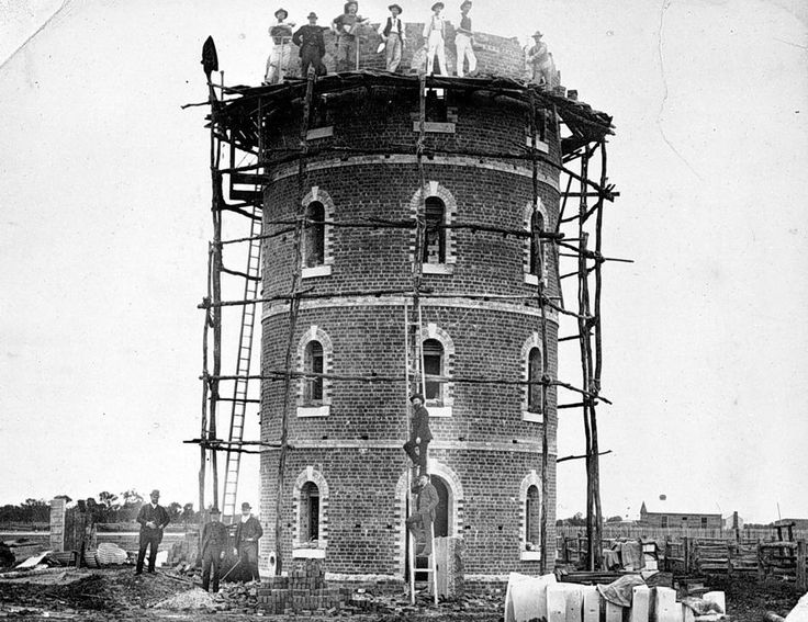 The Donald water tower under construction in 1887. There is scaffolding around the tower and workmen are laying bricks at an upper level. The tower was demolished in 1918 and site became the ladies croquet green.