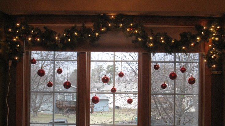 Hang Christmas Ornaments (not glass) in your living room window with gift wrap ribbon.