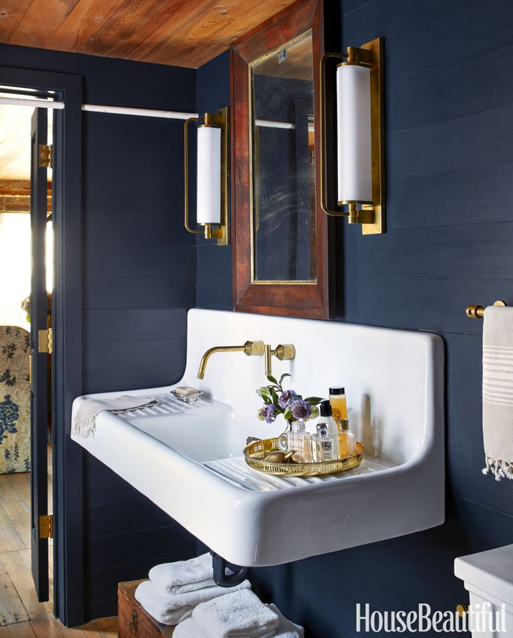 The farmhouse sink in the guest bathroom is a subtle nod to this Southern home's earlier days as a kitchen house. The white earthquake rod running through the doorway was uncovered during the renovation; it was put in for structural stability after an earthquake rocked Charleston in 1886. Benjamin Moore's Polo Blue on the walls adds a modern pop of color to this historic home.