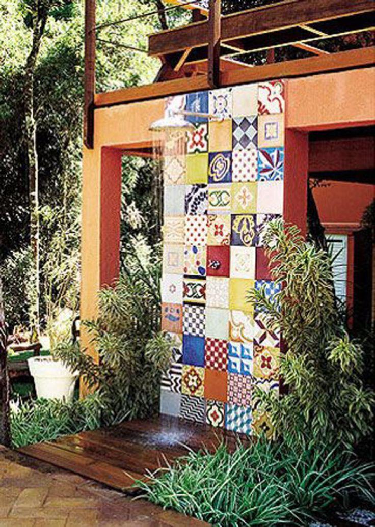Colorindo a fachada laranja, os ladrilhos revestem a parede do chuveiro externo, rodeado de plantas.