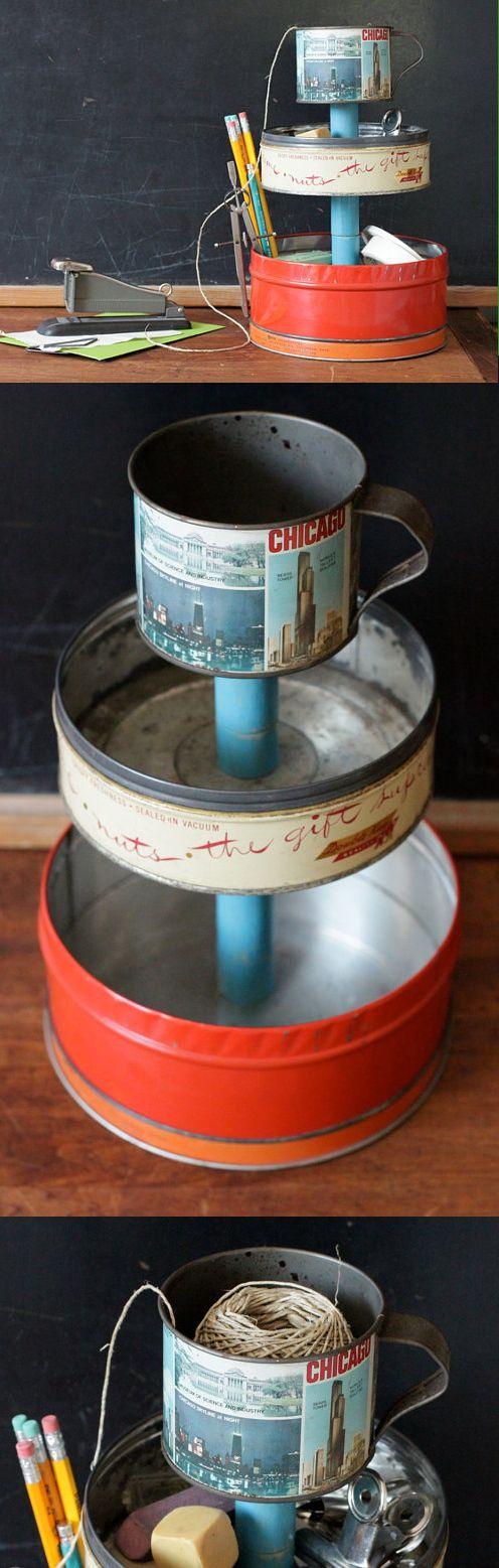 Tour de rangement faite avec des boites en fer fixées sur une tige en bois