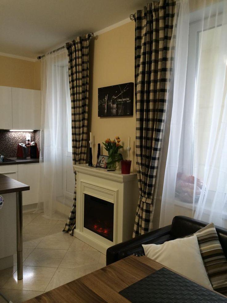 Белая кухня-столовая, клетчатые шторы, камин в гостиной