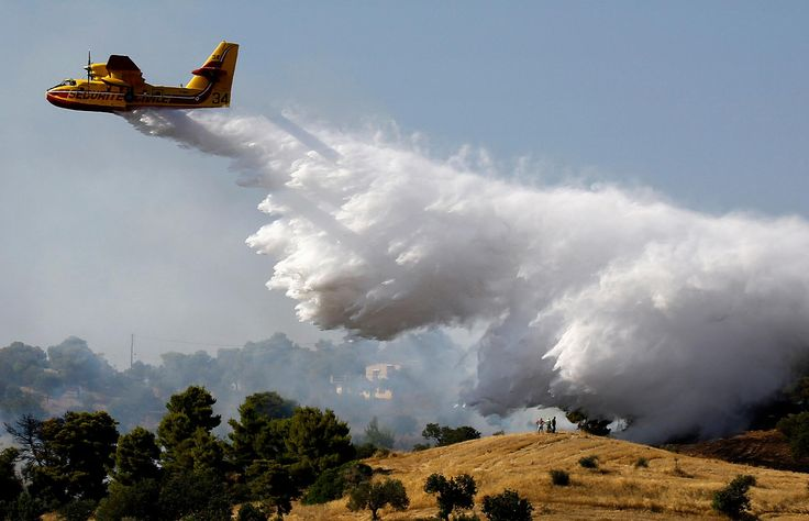 Guardian photographer of the year 2015: Yannis Behrakis | Locals watch a firefighting plane drop water over a fire near holiday homes in the village of Costa in southeastern Greece during a developing wildfire in July. Dozens were evacuated as firefighters fought the blaze